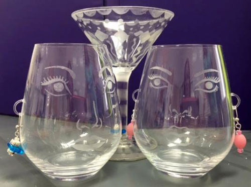 Two wine glasses etched with eyes, nose and mouth.